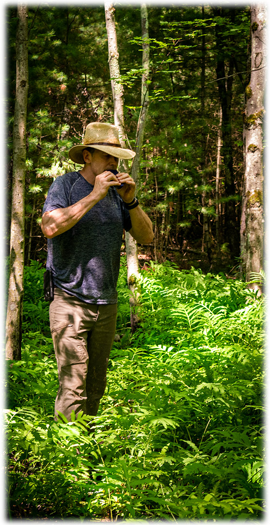 Man playing portable Coda EDC Flute in a beautiful forest.